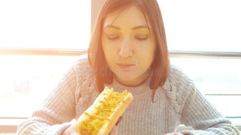 A mulher come um cachorro quente em um café do fast food com um apetite imagens de stock royalty free
