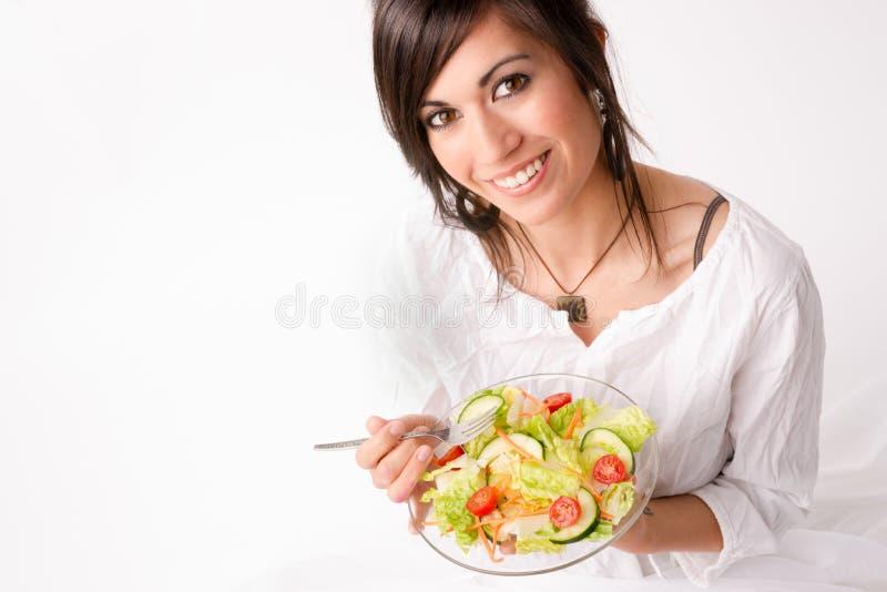 A mulher comendo saudável aprecia a salada verde fresca do alimento cru imagens de stock royalty free
