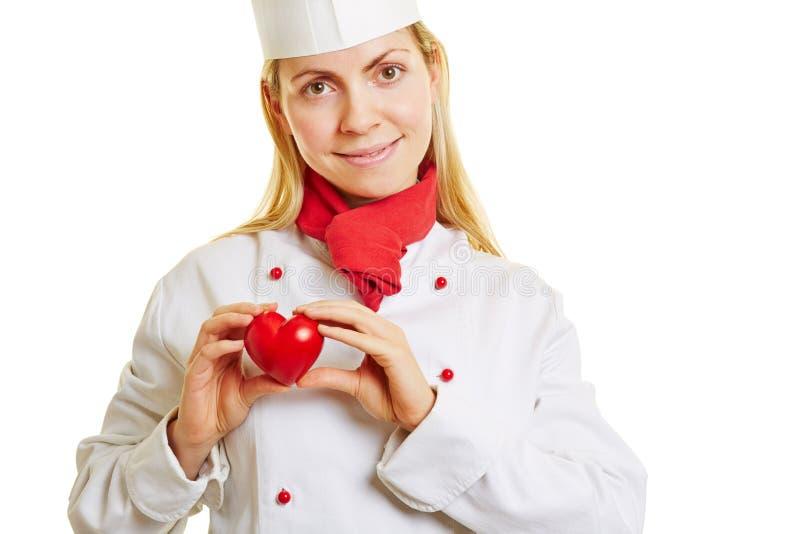 Mulher como o cozinheiro do cozinheiro chefe com coração vermelho fotografia de stock royalty free