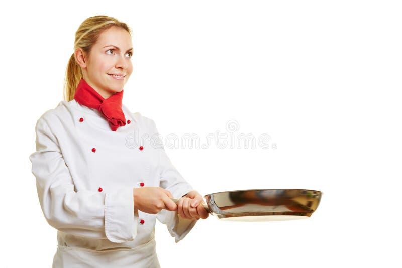 Mulher como o cozinheiro que cozinha com uma frigideira foto de stock