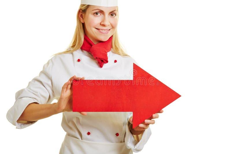 A mulher como um cozinheiro está guardando a seta imagem de stock royalty free