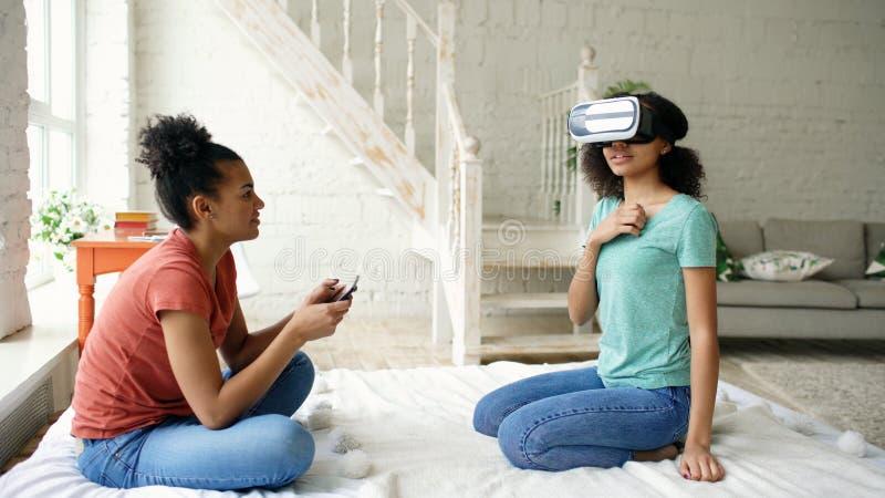Mulher competida misturada que usa vidros da realidade virtual quando seu amigo que guarda o tablet pc digital Vídeo do jogo das  imagem de stock
