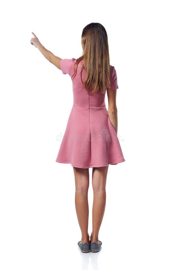Mulher completa do comprimento no vestido cor-de-rosa que aponta ao lado, vista traseira foto de stock royalty free