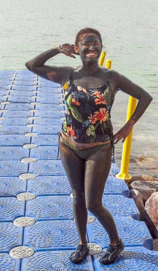 Mulher completamente da lama no Mar Morto imagens de stock