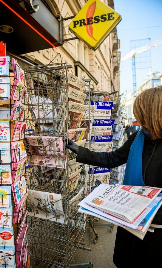 A mulher compra E.U., Reino Unido e o jornal alemão da imprensa de um newssta fotos de stock royalty free