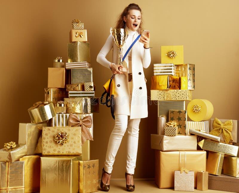 Mulher compradora com goblet dourado olhando para smartphone fotografia de stock