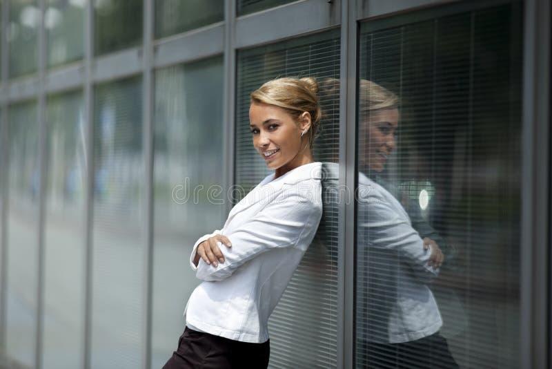 Mulher confiável que inclina-se no indicador do prédio de escritórios imagens de stock royalty free