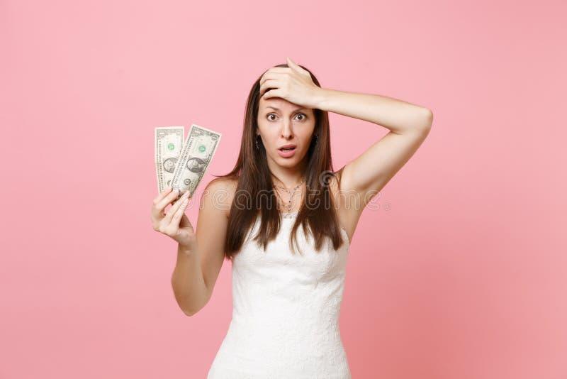 Mulher confundida da noiva no vestido de casamento branco que mantém a mão na testa que guarda as notas de dólar uma no rosa past foto de stock royalty free