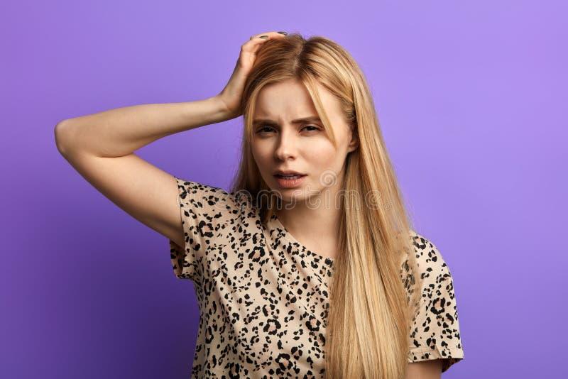 Mulher confundida nova, riscando sua cabe?a, pensando, sonhando acordado imagens de stock