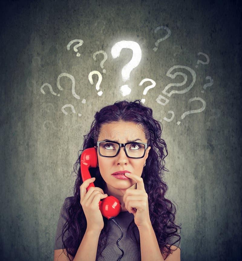 A mulher confundida preocupada virada que fala em um telefone tem muitas perguntas imagens de stock royalty free