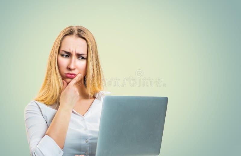 Mulher confundida que usa o portátil imagens de stock