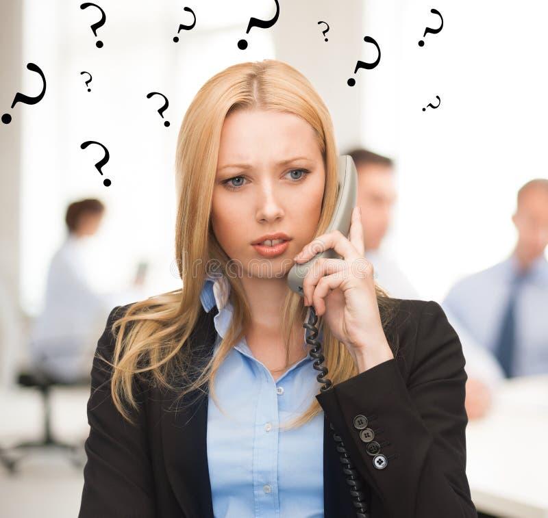 Mulher confusa com o telefone no escritório fotografia de stock