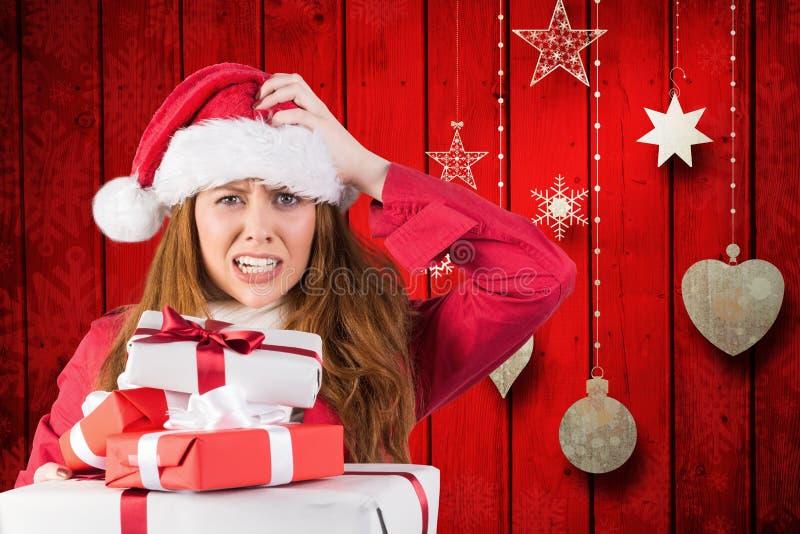 Mulher confusa no traje de Santa com uma pilha de presentes do Natal foto de stock royalty free