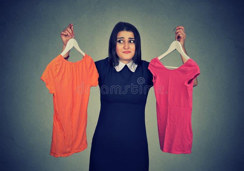 A mulher confusa que escolhe entre vestidos e não pode fazer a decisão imagem de stock