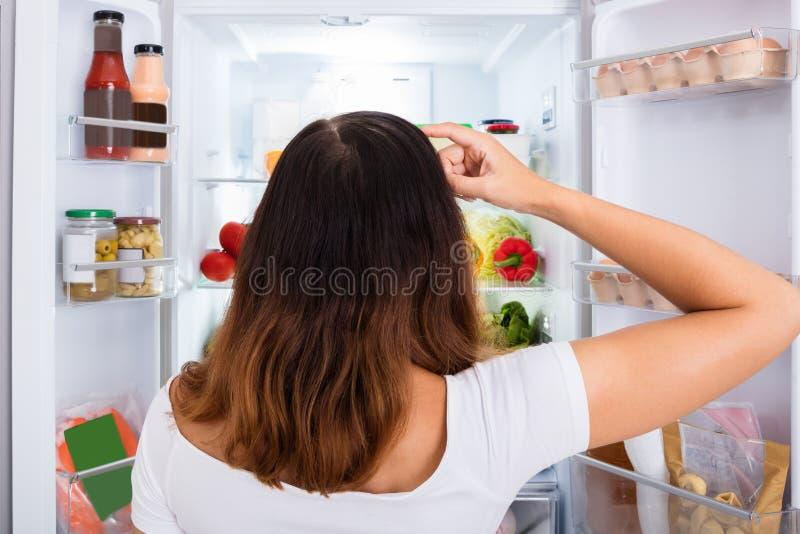 Mulher confusa que procura pelo alimento no refrigerador imagem de stock royalty free