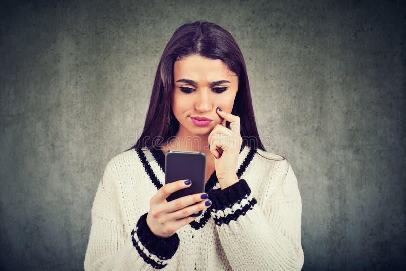 Mulher confusa que usa o telefone celular imagem de stock royalty free