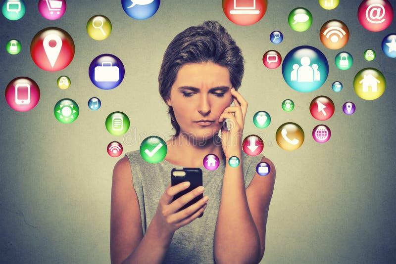 Mulher confusa que usa os ícones da aplicação do smartphone que voam fora do telefone celular fotografia de stock