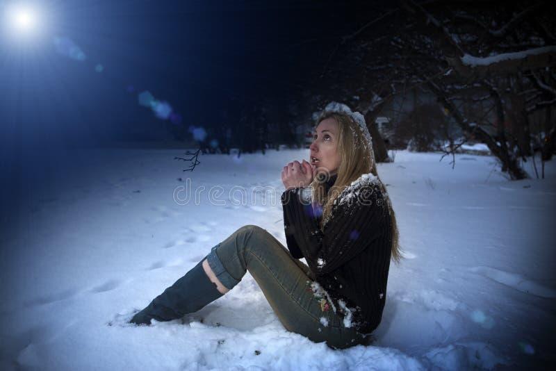 A mulher congelada bonita nova senta-se na neve no parque da noite imagens de stock royalty free