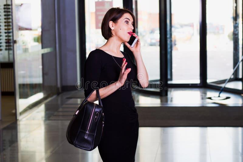 Mulher considerável que anda e que fala no telefone celular imagem de stock royalty free