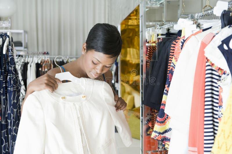 A mulher considera o revestimento branco na loja da roupa fotos de stock
