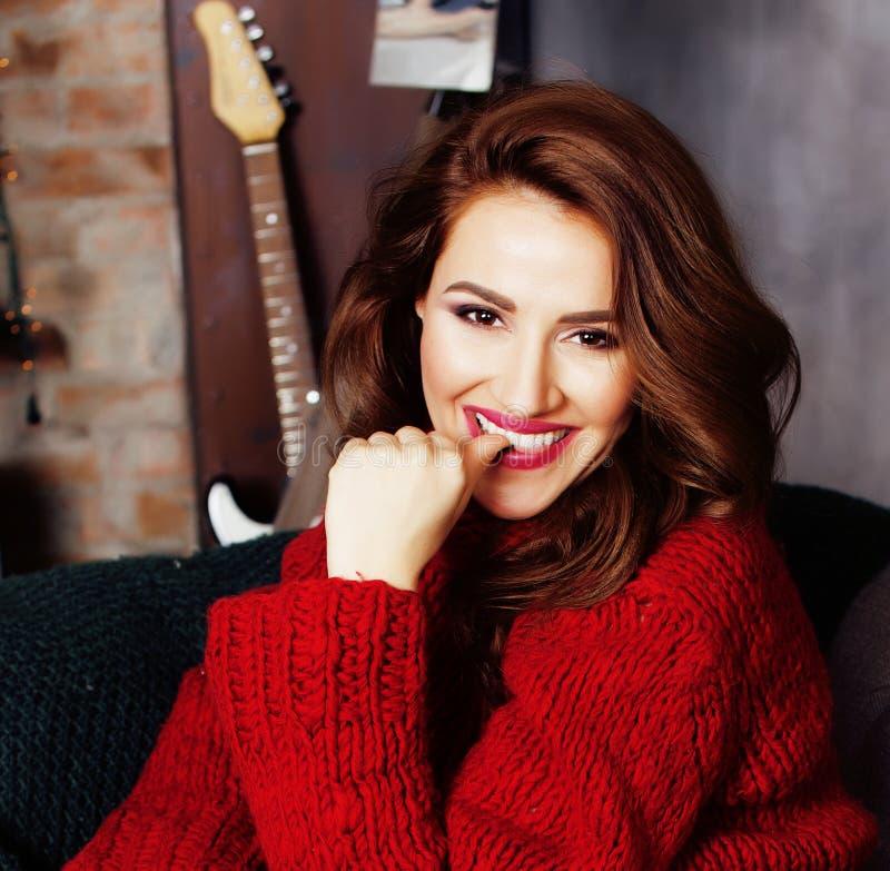 Mulher consideravelmente à moda dos jovens na camiseta vermelha do inverno no sofá no sorriso feliz interior home, conceito dos p imagens de stock