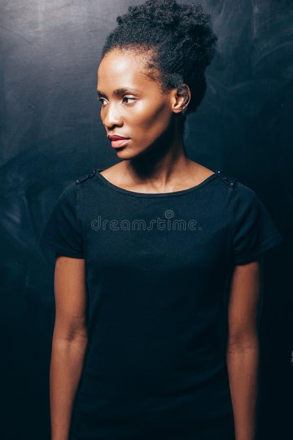 Mulher consideravelmente afro-americana no fundo escuro imagem de stock royalty free