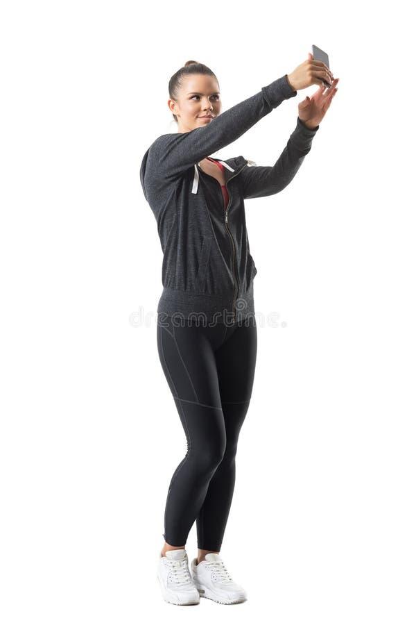 Mulher consideravelmente atlética relaxado dos jovens no sportswear que toma o selfie que olha o telefone fotografia de stock