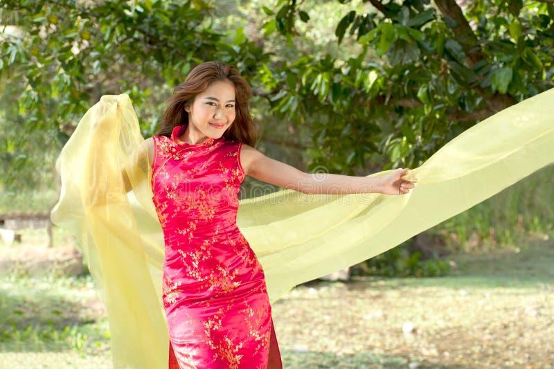 Mulher consideravelmente chinesa no vestido tradicional em uma maneira alegre fotografia de stock