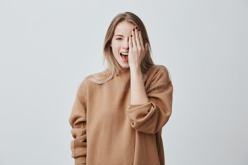Mulher consideravelmente encantador alegre na camiseta fraca com cabelo justo que sorri felizmente, tendo o divertimento dentro,  foto de stock royalty free