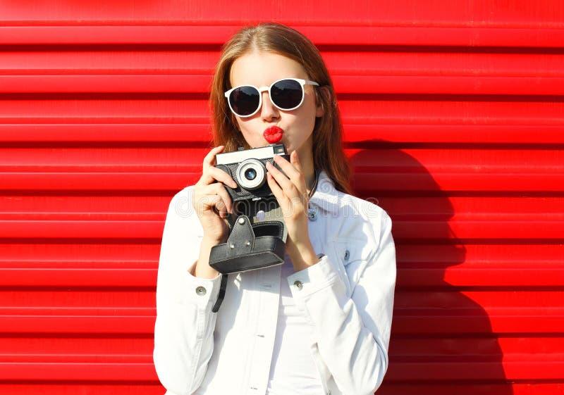 Mulher consideravelmente fresca com a câmera retro sobre o vermelho imagens de stock