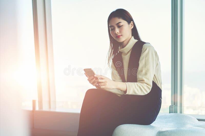 A mulher consideravelmente japonesa está jogando jogos no telefone celular durante o tempo da recreação fotos de stock royalty free