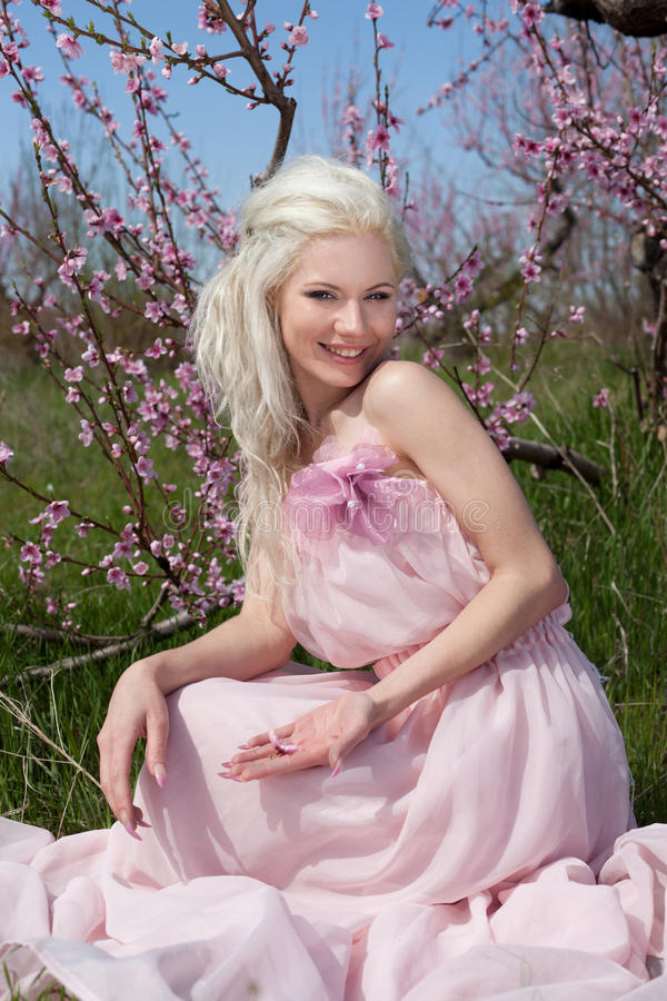 Mulher consideravelmente loura dos jovens no jardim de florescência imagem de stock