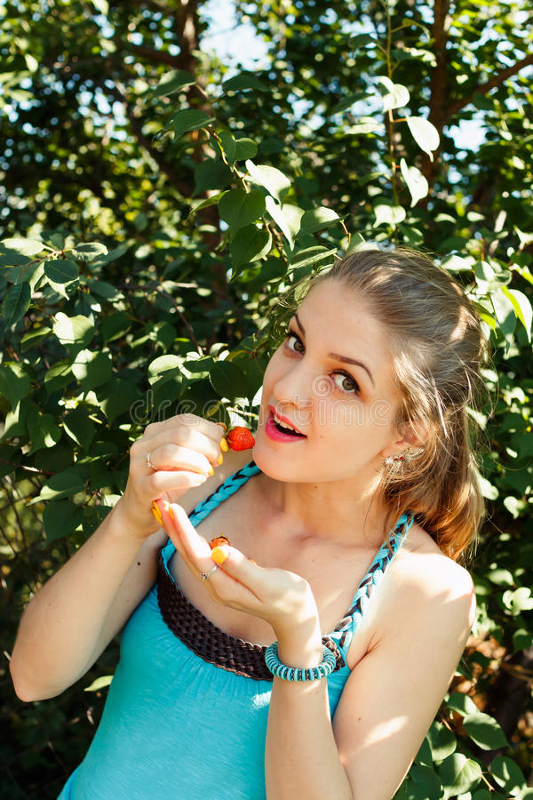 Mulher consideravelmente loura dos jovens que come a morango imagens de stock royalty free
