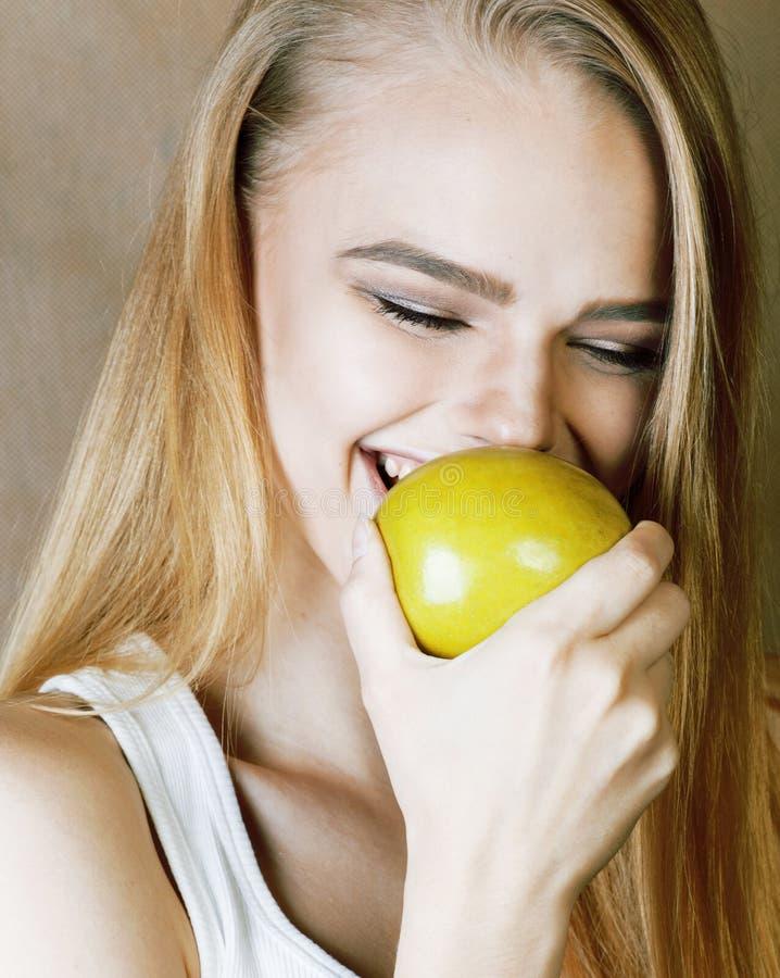 Mulher consideravelmente loura dos jovens que mantém o sorriso verde da maçã magro, lifes foto de stock