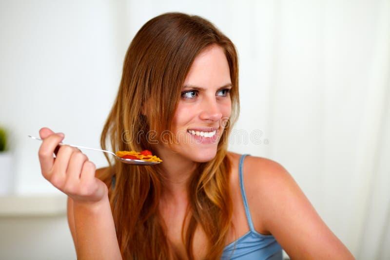 Mulher consideravelmente loura que come a refeição saudável imagem de stock