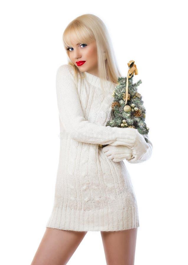 Mulher consideravelmente loura que prende a árvore de Natal pequena imagens de stock
