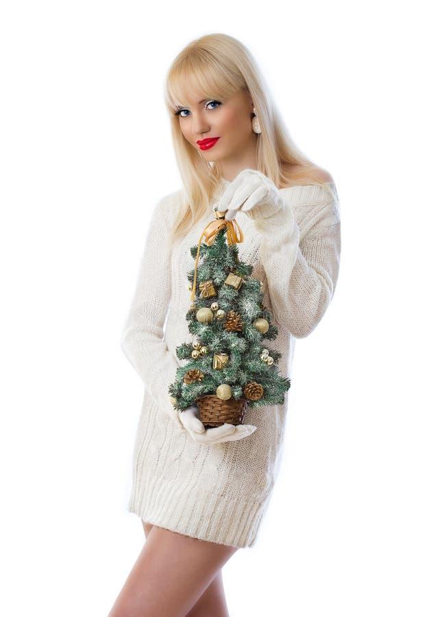 Mulher consideravelmente loura que prende a árvore de Natal pequena foto de stock royalty free