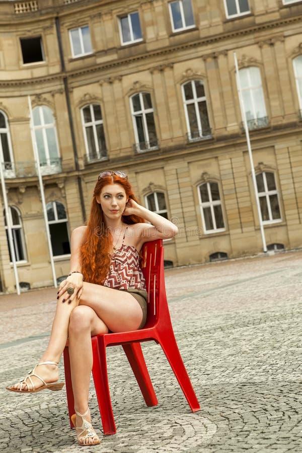 Mulher consideravelmente loura que senta-se na cadeira vermelha imagem de stock