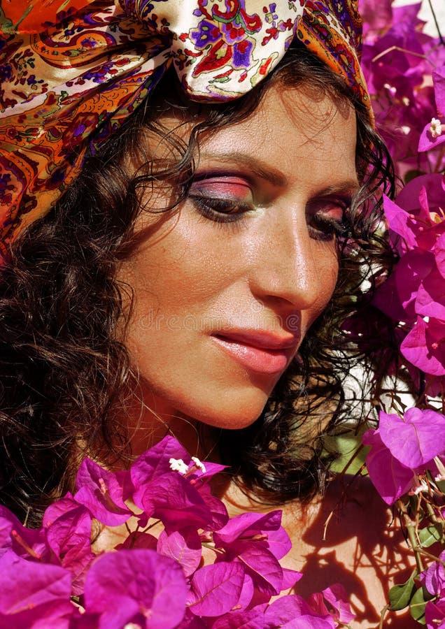 Mulher consideravelmente madura fora entre flores cor-de-rosa imagem de stock