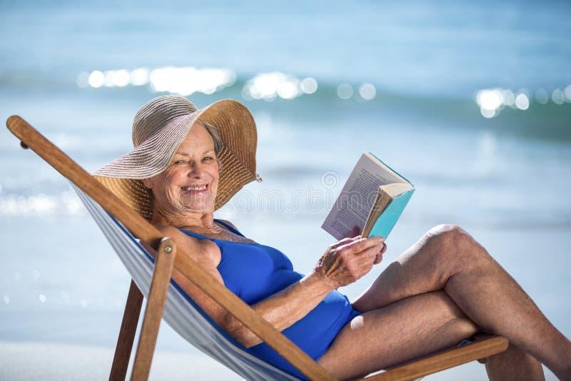 Mulher consideravelmente madura que lê um livro que encontra-se na cadeira de plataforma imagem de stock royalty free
