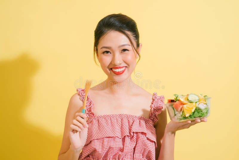 Mulher consideravelmente magro elegante que come a salada saudável imagens de stock royalty free