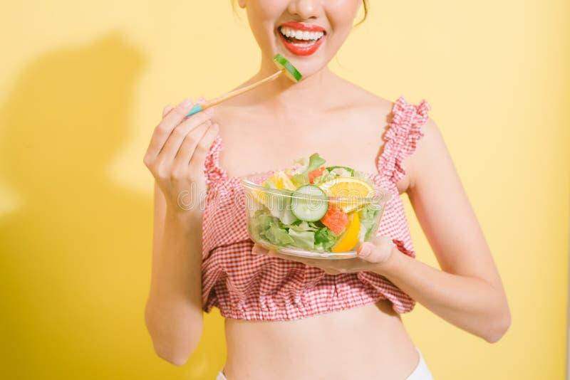 Mulher consideravelmente magro elegante que come a salada saudável foto de stock royalty free