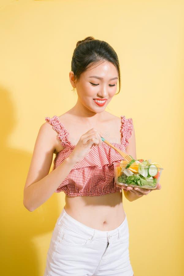 Mulher consideravelmente magro elegante que come a salada saudável foto de stock