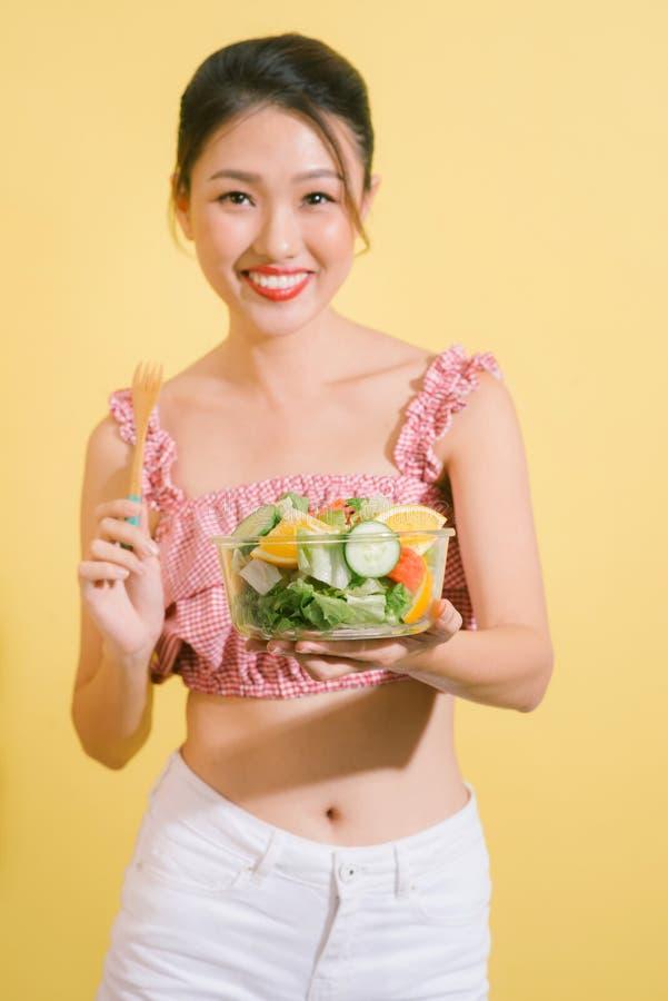 Mulher consideravelmente magro elegante que come a salada saudável imagens de stock