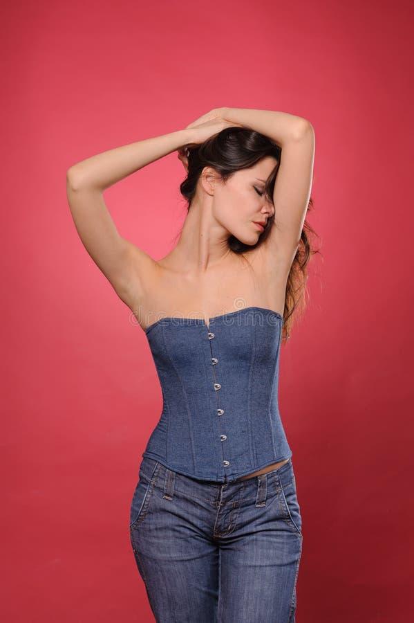 Mulher consideravelmente nova com a cintura magro no espartilho de brim imagens de stock royalty free