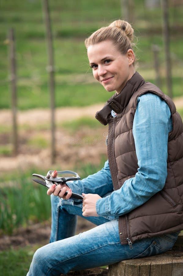 Mulher consideravelmente nova do fazendeiro com a ferramenta de ramos do corte na mola F fotos de stock