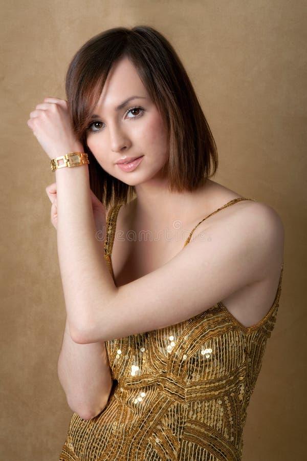 Mulher consideravelmente nova no vestido do ouro com relógio de ouro imagens de stock royalty free