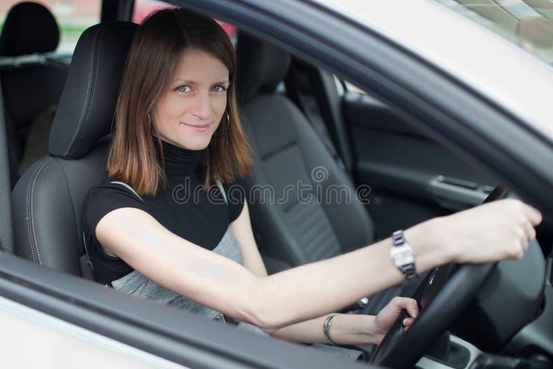 Mulher consideravelmente nova que conduz seu carro fotografia de stock