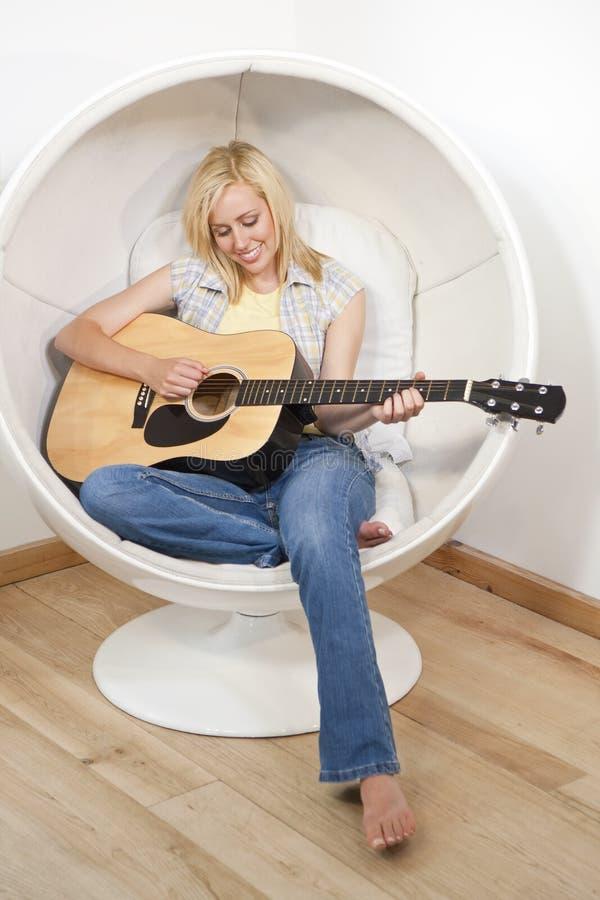 Mulher consideravelmente nova que joga a guitarra na cadeira da bolha imagem de stock royalty free