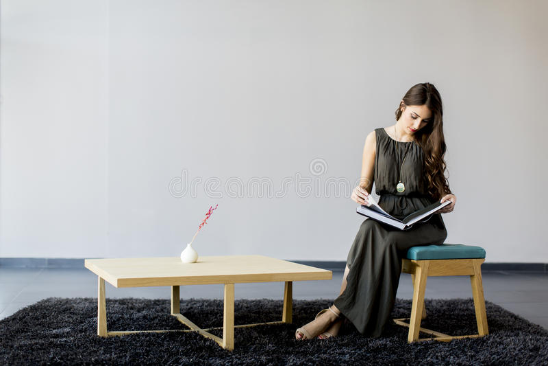 Mulher consideravelmente nova que lê um livro foto de stock royalty free